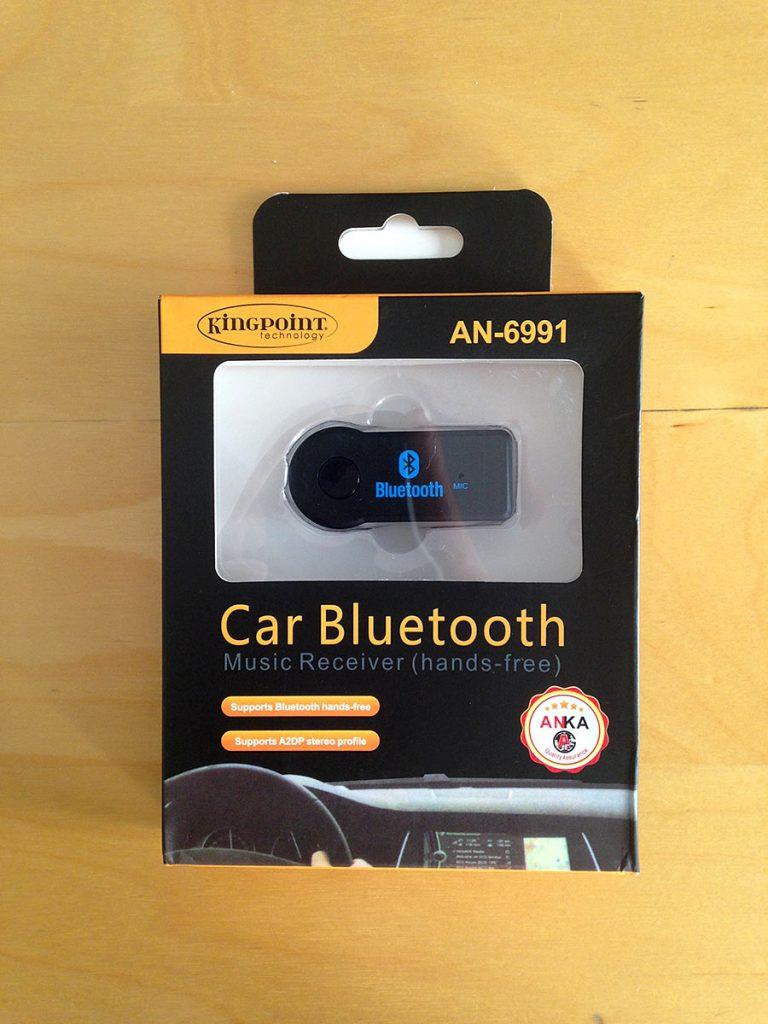 Arabada bluetooth ile telefondan müzik dinlemek için iPhone Samsung Lg Bluetooth Aux Araç Kiti kutusu. Kutunun penceresinden bluetooth alıcı görünüyor.