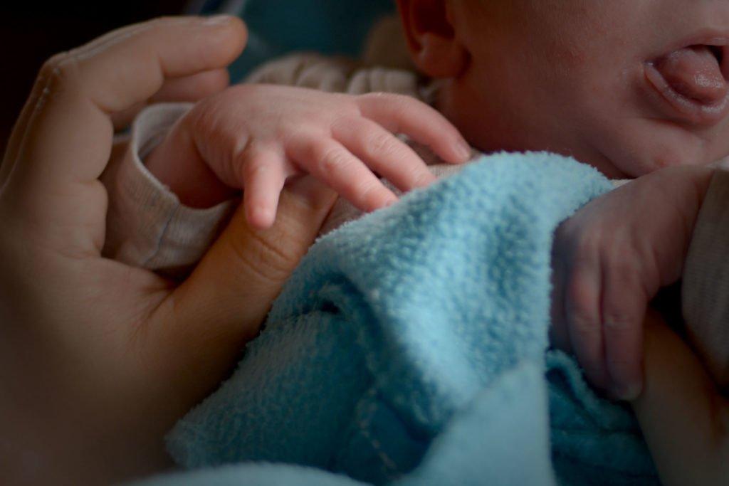 Evde doğum ardından annesi bebeğinin ellerini tutuyor.